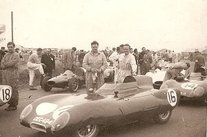 John Crosthwaite - Lotus Elevens at British Grand Prix, Silverstone. Formula 2 race, July 1956. Crosthwaite holding cloth. Driver car no.16, Cliff Allison leaning on car. Driver car no.18, Graham Hill standing on left. Roy Salvadori standing with foot on tyre of Cooper T41