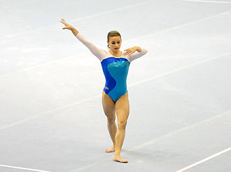 Glossary of gymnastics terms - Jade Barbosa performing her floor routine during a gymnastics competition. The white lines indicate the bounds of the floor.