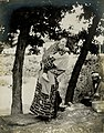 Japanese Ainu mother and child from the Department of Anthropology at the 1904 World's Fair. (Woman carrying child on her back; man with basket in right background).jpg