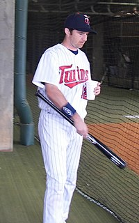 "A man in a white pinstriped baseball uniform with ""Twins"" on the chest holds a baseball bat and a cup."