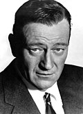 Black and white portrait of John Wayne—a white man with a broad forehead, dark straight hair and dark eyes, wearing an elegant suit, around 58 years of age—in 1965.
