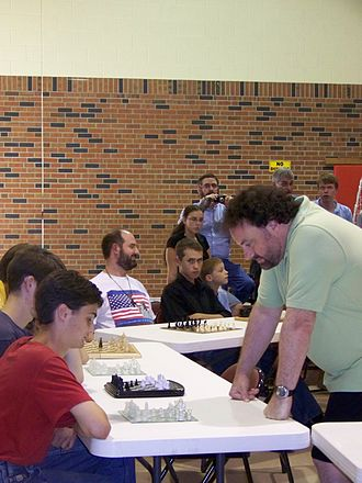 Jonathan Sarfati - Sarfati playing chess against multiple players at a creation conference, 2011.