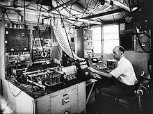Monochrome photograph of man in room with electronic equipment and many cables straggling from the ceiling and elsewhere, with his hand on a black machine.