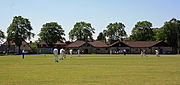 Cricket being played in front of the pavilion at Knowle Cricket Club Ground