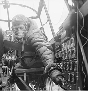Flight engineer - The flight engineer on an Avro Lancaster checks settings on the control panel from his seat in the cockpit