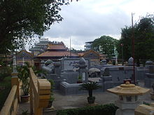 A cemetery with densely packed headstones made of cement. Almost no grass or flora can be seen. Many of the headstones are elaborate with a yellow or orange-tiled roof in the manner of an East Asian temple.