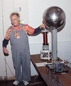 A man wearing coveralls with his left hand near the metal sphere of a Van de Graaff generator. His hair is standing on end due to electrostatic repulsion.