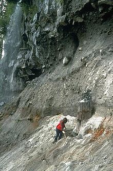 A rocky cliff with a person at its base.