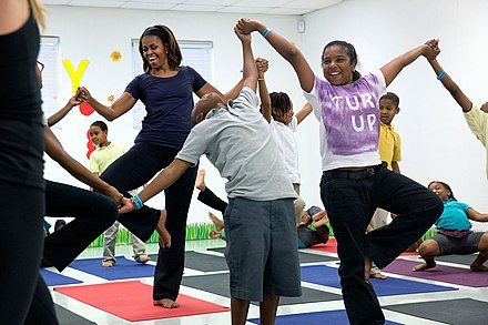 "Michelle Obama joins children for a yoga class during a ""Let's Move!"" after school activities event. Michelle Obama joins children for a yoga class during a ""Let's Move!"" after school activities event, 2014.jpg"