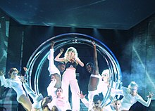 A blond woman in white pants and black bustier stands inside a number of metallic circular rings. She holds a microphone to her mouth with her left hand and her right hand makes a claw like gesture. The woman is flanked by men and women in white dress and fierce expressions with their eyes being white in color.