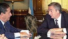Kirchner parolante al prezidanto Eduardo Duhalde ĉe tablo