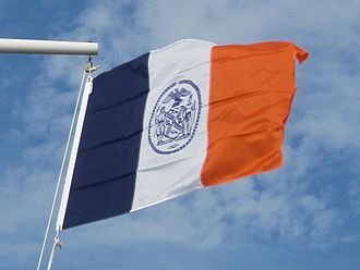 Flags of New York City - The flag unfurled and fluttering, mounted on a city park yardarm.