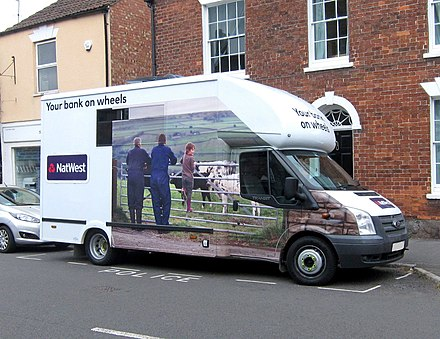 A NatWest mobile banking van in the town of Berkeley, Gloucestershire, England. The van visits Berkeley for two hours each Thursday following the closure of the town's NatWest branch in 2015. NatWest banking van at Berkeley, Glos, England 2Aug2018 arp.jpg