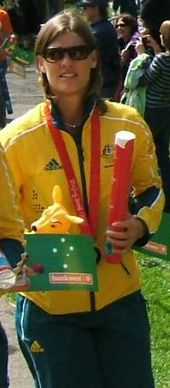 A standing blonde woman wearing sunglasses, a green and yellow track suit, and a bronze medal, while holding a plush kangaroo.