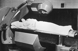 External beam radiotherapy - Patient receiving cobalt-60 therapy in an early teletherapy machine, probably early 1950s.  The cobalt is in the radiation head (top center), which produces a beam of gamma rays which penetrate the patient's body and strike the tumor.  Radiation passing through the patient is absorbed by the lead shield opposite. During therapy, the head unit rotates slowly around the patient to reduce the radiation dose to healthy tissue.
