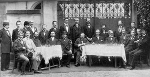 Nuremberg 1896 chess tournament - Standing: Standing: Lasker, Charousek, Schlechter, two organisers, Janowsky, Maróczy, Marco, Showalter, three organisers. Seated: Albin, Porges, Chigorin, Tarrasch, Winawer, Steinitz, Blackburne, Schallopp, Schiffers, Pillsbury, Walbrodt, Teichmann