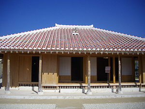 Okinawa Prefectural Museum - Reproduction of a traditional Okinawan home, erected in front of the museum. The red ceramic roof tiles and shisa lion-dog are particularly distinctive of traditional Okinawan architecture.