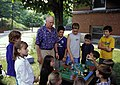 Older person shows how a watershed works to a group of school children.jpg