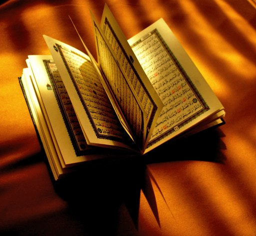 A paper Quran opened halfwise on top of a brown cloth