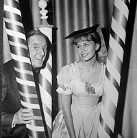 publicity shot of elderly man and young female sitting between three poles