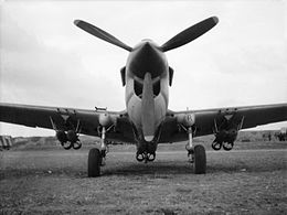 Low-angle front view of single-engined military aircraft with three-bladed propeller and six bombs beneath the wings and fuselage