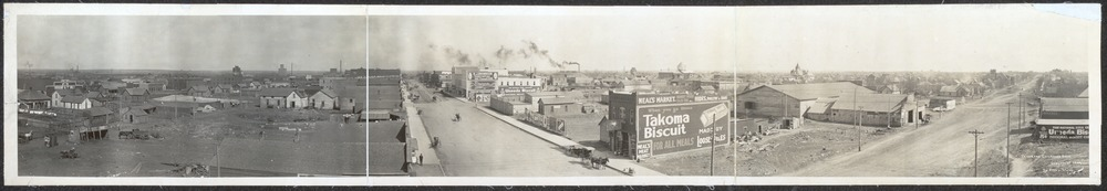 A panoramic view showing wooden houses and businesses, many along two main dirt roads that meet at a corner.