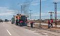 Personas realizando trabajos de reparación de manto asfaltico en la Avenida Juan Bautista.JPG