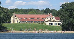 Big hotel with beach on lake.