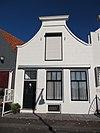 foto van Huis met door lijstje afgesloten gecementeerde klokgevel, in blokken gevoegd