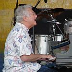 Right side view of a man who is wearing glasses and a white shirt with distinctive patterns playing the piano. Several steel drums are seen behind the piano.