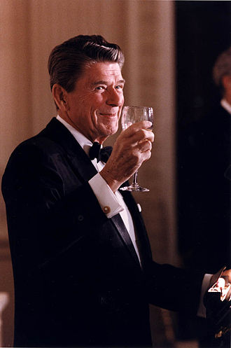 Black tie - Former U.S. President Ronald Reagan toasting in a dinner suit, i.e., a tuxedo with peak lapels, turnover collar dress shirt with double cuffs, and a black bowtie