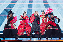 Madonna and her dancers in Japanese dresses, holding fans in their hand