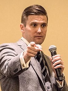 A photograph of Richard Spencer holding a microphone and pointing