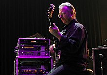 Robert Fripp ergonomically plays electric guitar while sitting in a posture developed through years of application of the Alexander Technique.