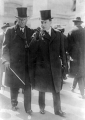 An image of John D. Rockefeller and John D. Rockefeller, Jr. walking down a street.