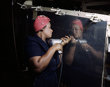 "A real-life ""Rosie the Riveter"" operating a hand drill at Vultee-Nashville, Tennessee, working on an A-31 Vengeance dive bomber."