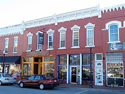 Two-story, red brick building with two distinct store fronts