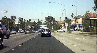 Santa Clarita, California - A typical stretch of Valencia Boulevard in the Valencia part of Santa Clarita in July 2004. The bridge in the distance carries a paseo (a type of dedicated pedestrian pathway) over the roadway.