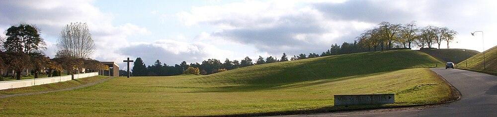 """Skovkirkegårdens """"bibelske landskab"""" [6] [a] med Skovkrematoriet til venstre og Elmehøjden til højre.   Vy fra hovedentréen mod syd i november 2009."""
