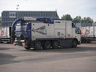 Suction excavator - Vacuum waste collection vehicle. Waste suction apparatus from R98 (a municipal cleansing company in Copenhagen in Denmark). The tube on the top is connected to a connecting piece kept under the pavement, and the waste is sucked out from a tank placed in a strategic place in the neighborhood.
