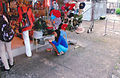 Squatting saleswoman for her shop Vietnam.jpg