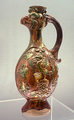 A Tang Dynasty earthenware vase with three-color (sancai) glaze and a bird head spout.