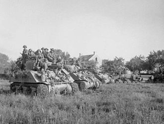 Operation Goodwood - Two M4 Sherman tanks, a Sherman Firefly carrying infantry and a Sherman Crab wait for the order to advance at the start of Operation Goodwood, 18 July
