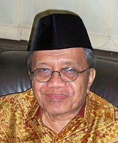 An older Indonesian man in a peci. He is wearing glasses and a batik shirt