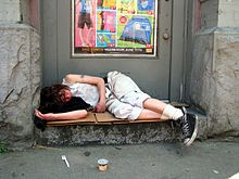 A young person sleeping in a doorway in a DTES alley