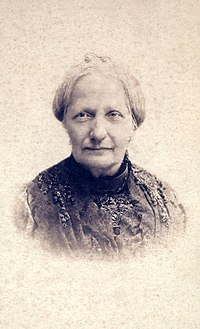 Head and shoulders sepia photograph showing an older woman with gray hair and wearing a dark lace dress