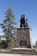 Photograph of a memorial at the Donner Camp, a set of bronze figures, woman, man, and child, atop a tall stone plinth.