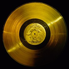 Flat circular disc of gold, with a central label, a hole, and a wide band of very small lines, like a golden version of an old analog record
