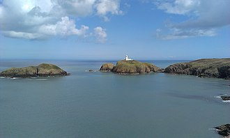 Strumble Head - Strumble Head lighthouse, looking across Carreg Onnen Bay. The island to the left of the lighthouse is Ynys Onnen (Ash Tree Island).