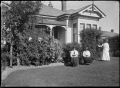Three unidentified women in a garden, beside a villa with verandah partially visible. ATLIB 284422.png